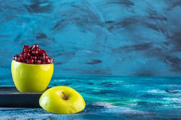 Нарезанные яблоки и гранатовые орехи на деревянной тарелке