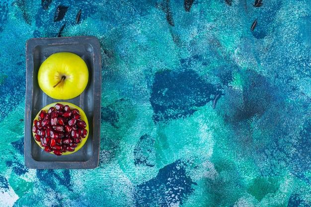 木の板にスライスしたリンゴとザクロの仮種皮
