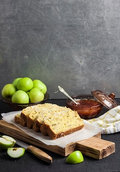 Sliced apple and coconut oaf cake on wooden cutting board on dark background. copy space