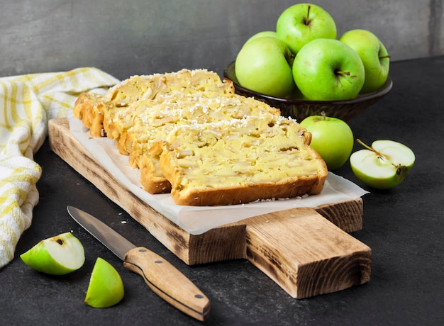 Sliced apple and coconut oaf cake on wooden cutting board on dark background