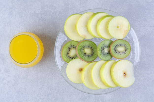 Sliced apple and kiwi on a glass pedestal next to a glass of orange juicy , on the marble table.