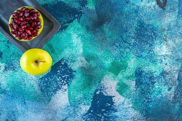 Arilli di mela e melograno affettati su un piatto di legno