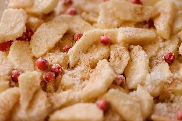 Нарезанные яблоки и клюква, посыпанные сахаром и корицей, готовы для приготовления яблочного пирога. готовим дома.