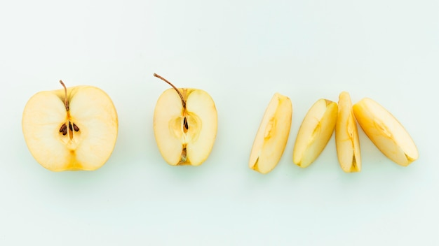 Sliced apples on pale blue background