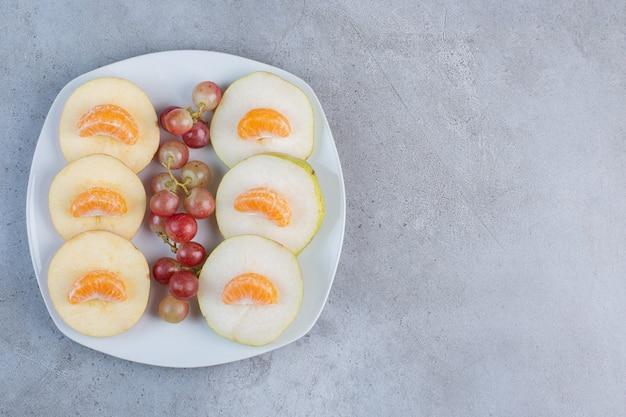 大理石の背景の大皿にスライスしたリンゴ、梨、みかん、ブドウ。