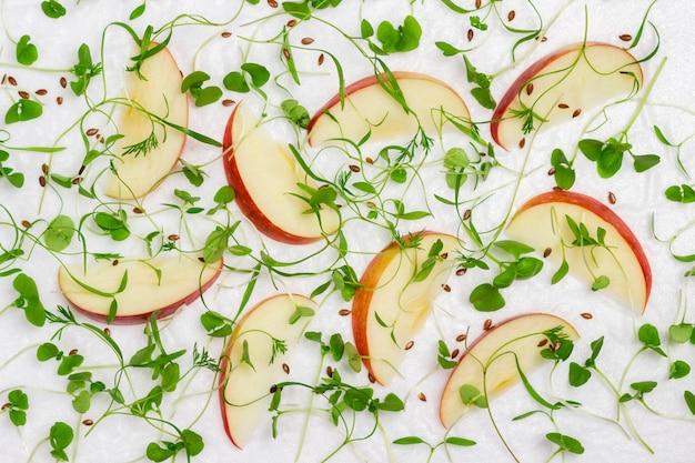Нарезанные яблоки с молодыми ростками микрозелени на белом фоне, здоровое питание.