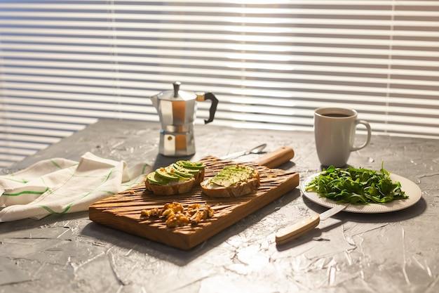 Нарезанный авокадо на тостовом хлебе с орехами и кофейным шпинатом на тарелке и завтрак в горшочке мока и