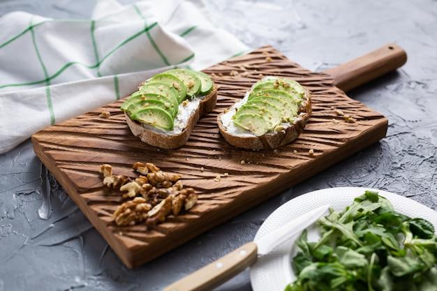 トーストパンにアボカドをナッツでスライスしました。朝食と健康食品のコンセプト。