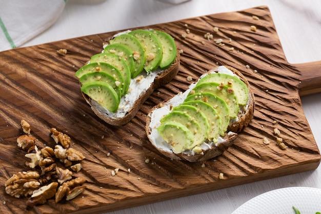 Нарезанный авокадо на тостовом хлебе с орехами на завтрак и концепция здорового питания