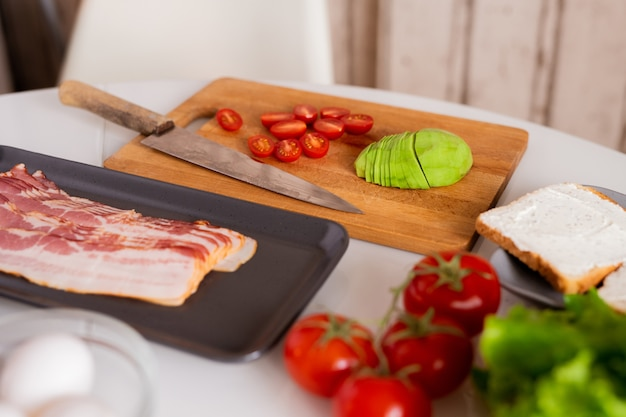 Sliced bacon, avocado and tomatoes on kitchen table in process of cooking healthy breakfast and two sandwiches on plate near by