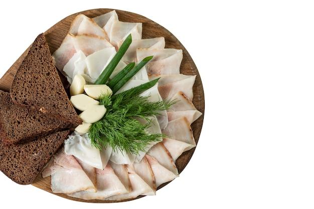 木製のサービングボードにニンニク、ハーブ、パンをスライスしたベーコン。ロシア料理とウクライナ料理の伝統的な前菜。閉じる。上面図。白い背景で隔離。テキスト用のスペース。