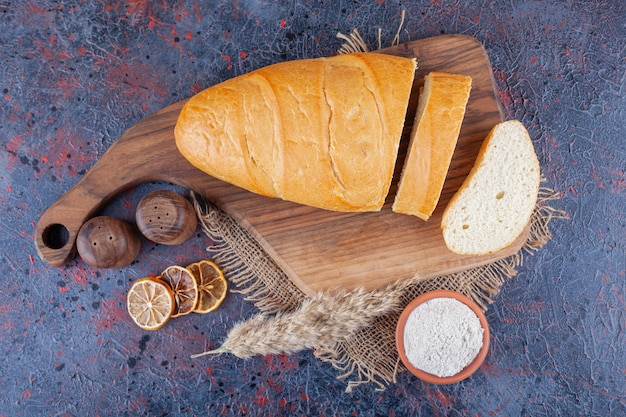 Нарезанный хлеб багет на борту на полотенце на синем.