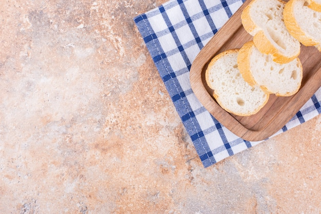 대리석에 수건에 나무 접시에 바게트 슬라이스.