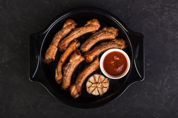 구운 돼지 갈비를 베이킹 접시에 마늘과 붉은 소스와 함께 썰었습니다.