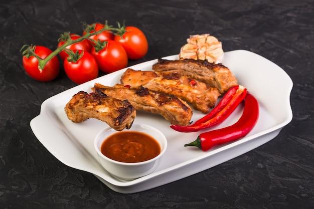 고추와 빨간 소스와 토마토와 함께 하얀 접시에 구운 돼지 갈비를 슬라이스