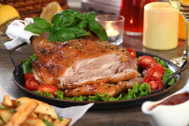 Нарезанная запеченная голень индейки на овощном подносе за обеденным столом в день благодарения