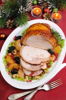 クリスマステーブルにフルーツガーニッシュとスライスした焼きターキーハム Premium写真