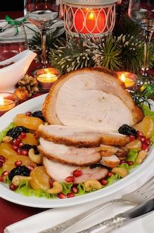 クリスマステーブルにフルーツガーニッシュとスライスした焼きターキーハム
