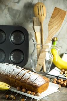 Sliced banana bread is lying on a board among kitchen utensils, bananas and hazelnuts