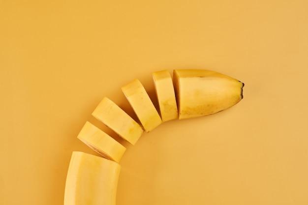 Нарезанные бананы на желтом фоне крупным планом, ингредиент здорового десерта Premium Фотографии