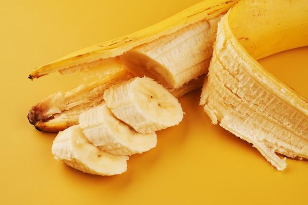 Нарезанные бананы на желтом фоне крупным планом, ингредиент здорового десерта