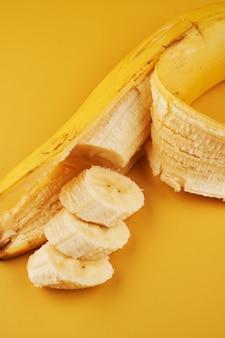 노란색 배경에 얇게 썬 바나나, 건강한 디저트 재료