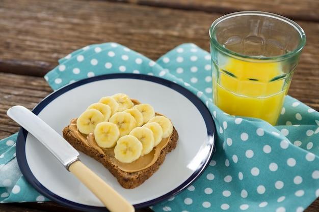 나무 테이블에 주스 한 잔과 함께 접시에 갈색 빵에 확산 슬라이스 바나나