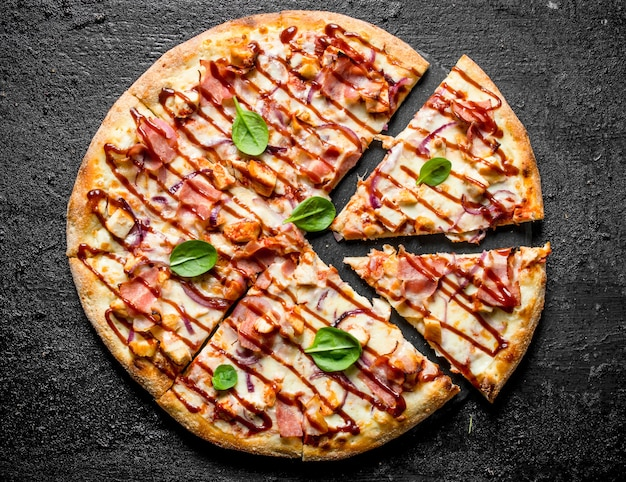 Sliced barbecue pizza with spinach leaves on black rustic table