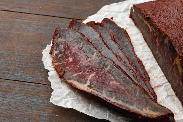 Нарезанное мясо бастурмы на деревянном фоне бровей