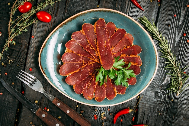 Sliced ​​basturma slices with herbs on a blue plate on a dark wooden background