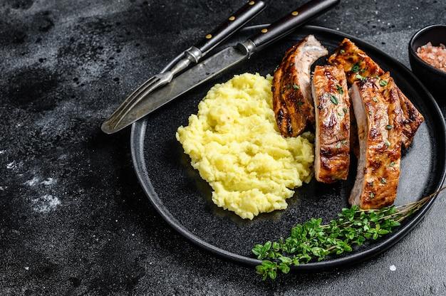 매쉬 포테이토와 함께 접시에 얇게 썬 바베큐 구운 돼지고기 랙 스페어 립. 검은 배경. 평면도. 공간을 복사합니다.