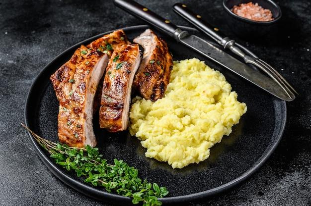 Нарезанные на гриле свиные ребрышки на тарелке с картофельным пюре. вид сверху.