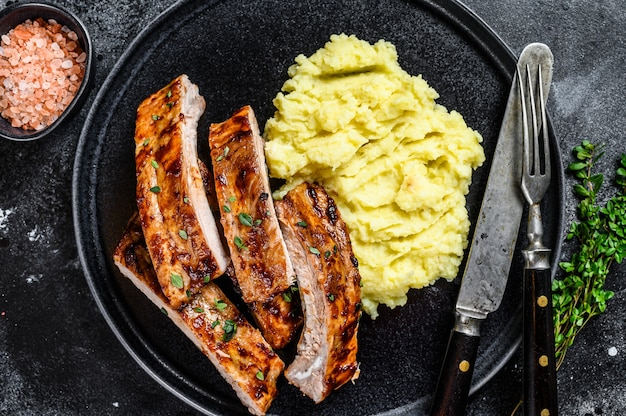 Нарезанные на гриле свиные ребрышки на тарелке с картофельным пюре.