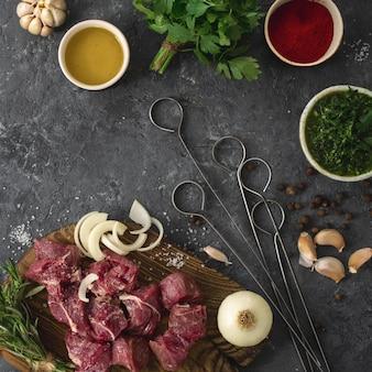 Кусочки филе говядины с овощами. кухонный стол с мясом и овощами на темном столе. ингредиенты приготовления мяса
