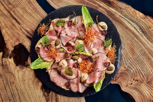 절인 야채와 소스를 곁들인 쇠고기 또는 돼지 고기 슬라이스. 아름답게 꾸며진 케이터링 연회 메뉴. 뷔페를위한 음식 간식 및 전채. 흰색 배경에