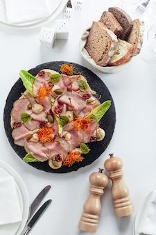 スライスした牛肉または豚肉のマリネ野菜とソース添え。美しく装飾されたケータリングバンケットメニュー。ビュッフェ用のフードスナックと前菜。白い背景に