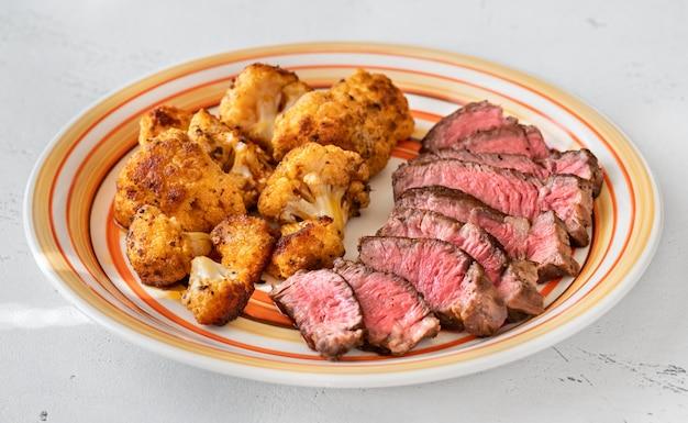 구운 콜리플라워 꽃 장식으로 장식된 얇게 썬 쇠고기 스테이크