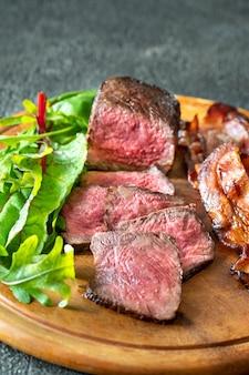 木の板に新鮮なルッコラの葉とベーコンの揚げたラッシャーのスライス ビーフ ステーキ