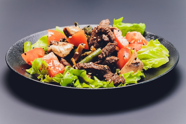 Sliced beef tagliata salad with green beans, cherry tomatoes, fresh arugula and parmesan and lime wedges, served on a black plate.