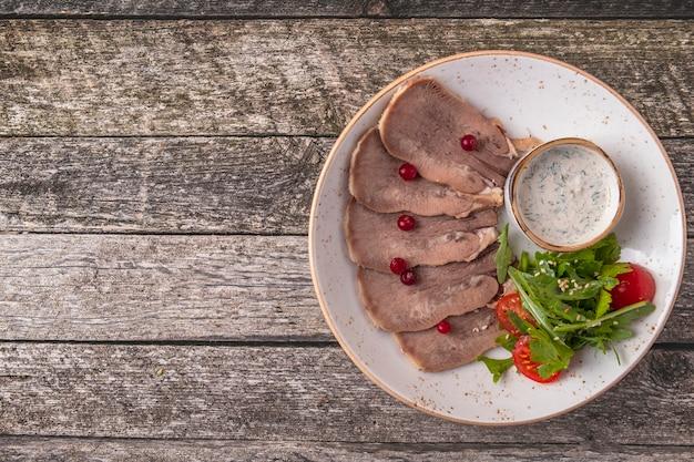 크랜베리, 양 고추 냉이 소스, 그린 샐러드를 곁들인 얇게 썬 쇠고기 혀.
