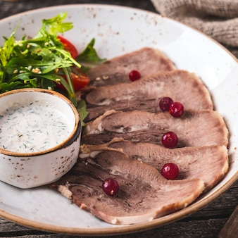 Sliced beef tongue with cranberry, salad and sauce