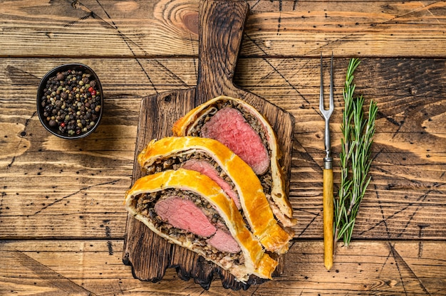 나무 커팅 보드에 쇠고기 웰링턴 생 과자를 슬라이스.