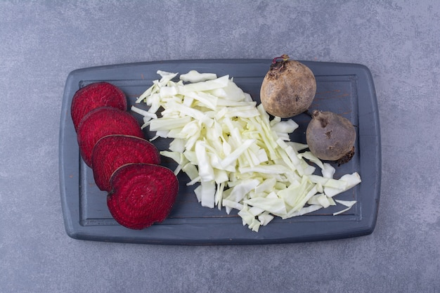 Sliced beetroot and chopped cabbage on a wooden board.