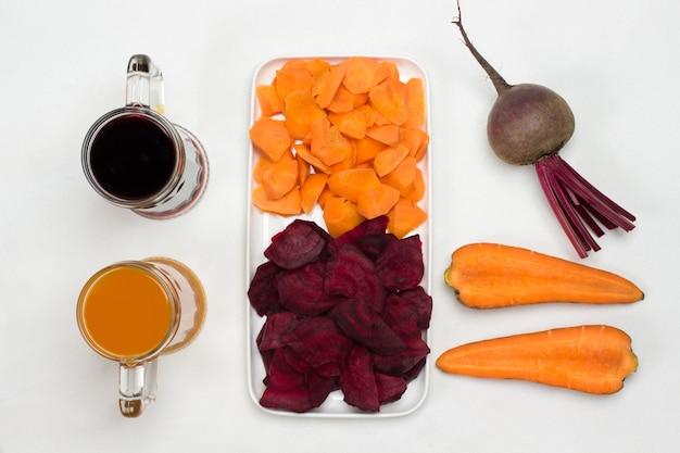白い皿にスライスしたビートとニンジン。ビートとニンジンの根菜。ビートルートとにんじんジュースを2杯。白色の背景。フラットレイ