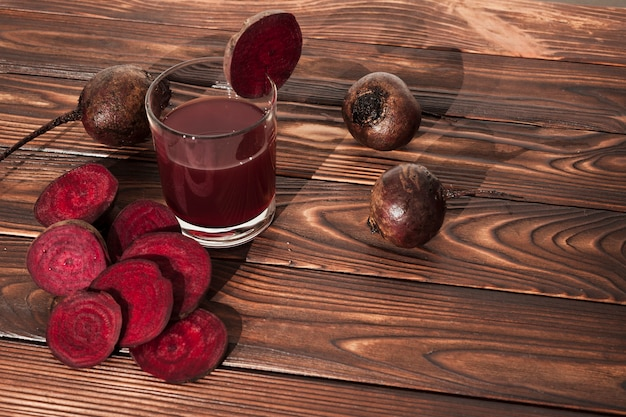 Sliced beets and juice on wooden surface