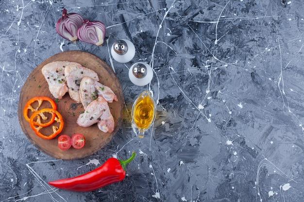 Нарезанный болгарский перец, помидоры и крыло на доске рядом с луком, солью и перцем на синем фоне.