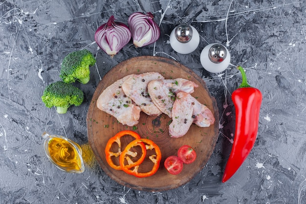 Sliced bell pepper, tomatoes and wing on a board next to onion, salt and pepper on the blue surface