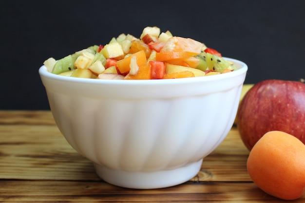다이어트 샐러드를 만들기 위해 얇게 썬 딸기와 과일이 접시에 있습니다. 나무 테이블에 체중 감량을위한 저칼로리 밝은 아침 식사.