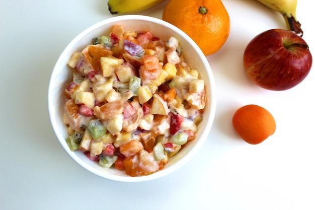 다이어트 샐러드를 만들기 위해 얇게 썬 딸기와 과일이 접시에 있습니다. 위에서 봅니다. 체중 감량을위한 저칼로리 밝은 아침 식사.