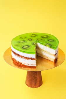 Sliced birthday cake decorated with green jelly and kiwi on top on the wooden cake stand. beautiful sponge cake with whipped cream. yellow background. copy space. food photography for recipe.